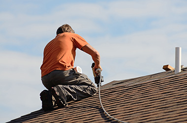 Man roofing a home